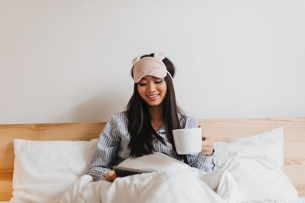 Dame en pyjama et masque de sommeil tient une tasse de thé et lit en position couchée dans son lit