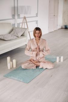 Une dame en pyjama pratique le yoga et s'assoit dans une pose spéciale sur un tapis à la maison