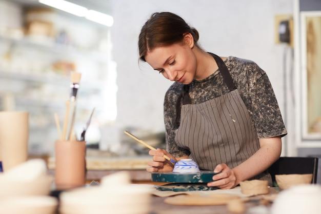 Dame qualifiée s'appuyant sur un bol en céramique