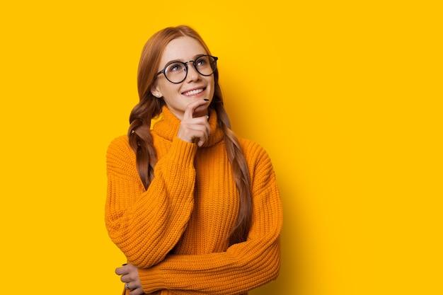 Une dame de race blanche au gingembre réfléchie touche son menton tout en regardant à travers des lunettes et posant sur un fond jaune dans un joli pull