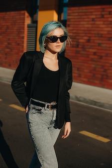 Dame de race blanche aux cheveux bleus avec des lunettes marchant à l'extérieur dans une journée de printemps ensoleillée