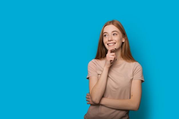 Dame de race blanche aux taches de rousseur aux cheveux rouges penser à quelque chose et sourire sur un mur bleu avec espace libre