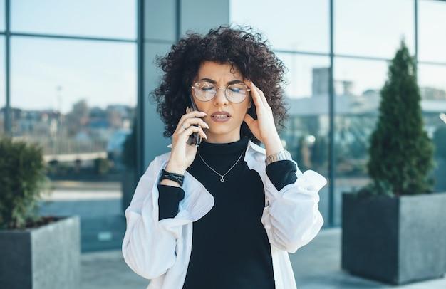 Dame de race blanche réfléchie avec des cheveux bouclés et des lunettes touchant ses cheveux et posant à l'extérieur lors d'une conversation téléphonique d'affaires
