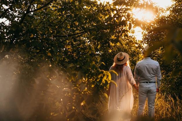 Dame de race blanche vêtue d'une robe blanche marche avec son amant dans un jardin plein d'arbres portant des chapeaux dans une soirée d'été