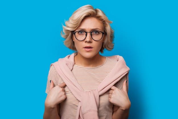 Dame regardant à travers des lunettes et pointant vers elle-même