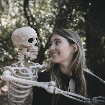 Dame riante regardant squelette