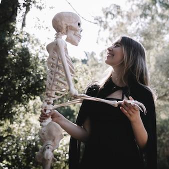 Dame riante en tenue de sorcière tenant un squelette
