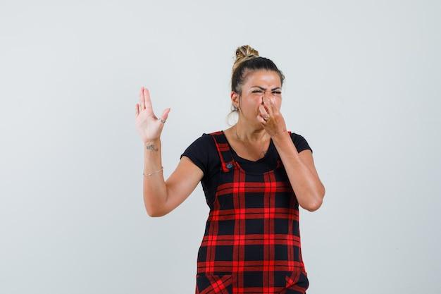 Dame en robe chasuble se pincer le nez en raison d'une mauvaise odeur et d'un air dégoûté, vue de face.