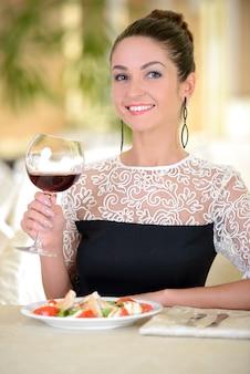 Dame en robe colorée, boire du vin, assis dans un restaurant