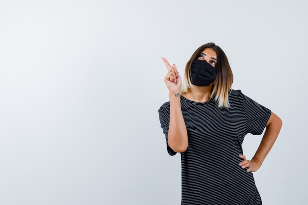 Dame en robe noire, masque médical pointant vers le coin supérieur gauche et regardant pensif, vue de face.