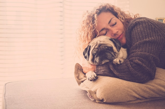 Dame romantique embrasse son meilleur ami vieux carlin sur le canapé qui dorment tous les deux ensemble dans l'amour et l'amitié