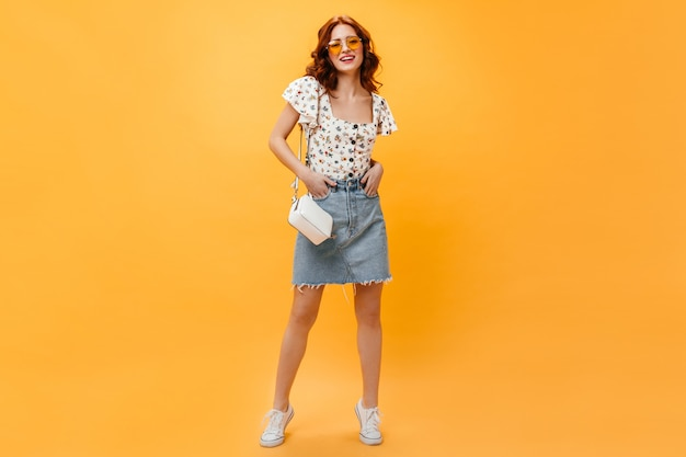 Dame rousse mignonne en jupe et t-shirt élégant avec sourire posant sur fond orange.