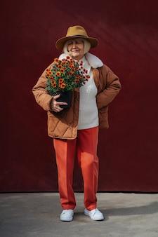 Dame senior élégante avec pot de fleurs. contenu femme âgée portant un pot avec des fleurs en fleurs