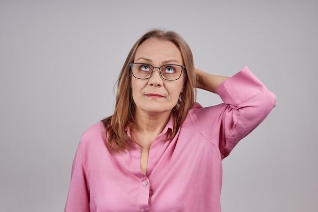 Dame senior préoccupée avec chemisier rose