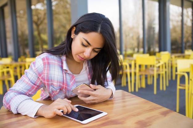 Dame sérieuse à l'aide de tablette et smartphone au café en plein air