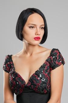 Dame sérieuse aux cheveux noirs courts et aux lèvres rouges qui pose en studio