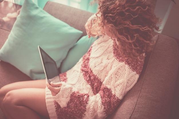 Dame seule à la maison avec des cheveux bruns bouclés regardant une tablette technologique connectée à internet pour vérifier les médias sociaux ou le travail ou un film
