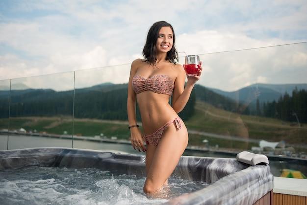 Dame sexy en bikini debout avec cocktail au jacuzzi