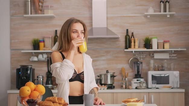 Dame sexy buvant du jus d'orange le matin pendant le petit déjeuner en lingerie noire. jeune femme blonde séduisante en sous-vêtements sexy avec des tatouages assis dans une cuisine moderne.