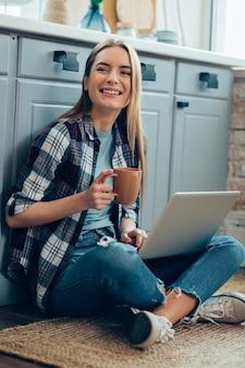 Dame souriante assise sur le sol avec un ordinateur portable et tenant une tasse tout en détournant les yeux