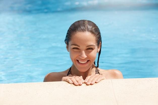 Dame souriante au bord de la piscine, femme aux cheveux noirs humides et sourire à pleines dents posant au bord de la piscine