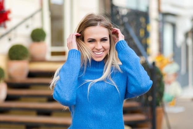 Dame souriante aux cheveux blonds s'amusant et riant dans la rue