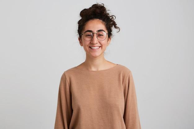 Dame souriante confiante, jolie femme aux cheveux bouclés foncés, portant un pull beige et des lunettes