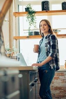 Dame souriante debout avec une tasse et un ordinateur portable dans sa cuisine confortable