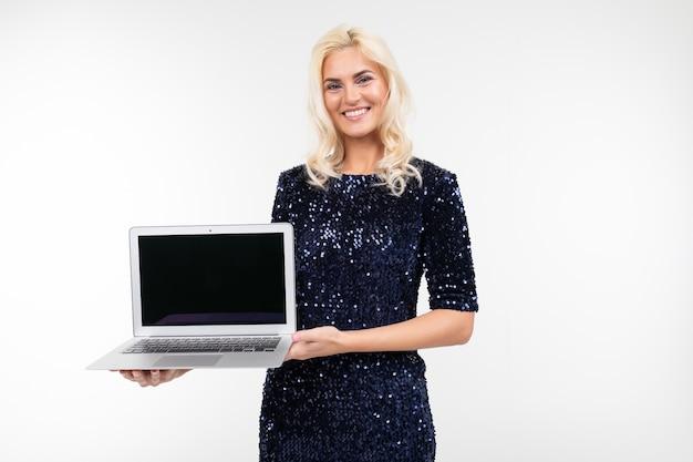 Dame souriante avec ordinateur portable avec maquette en mains sur fond blanc avec espace de copie