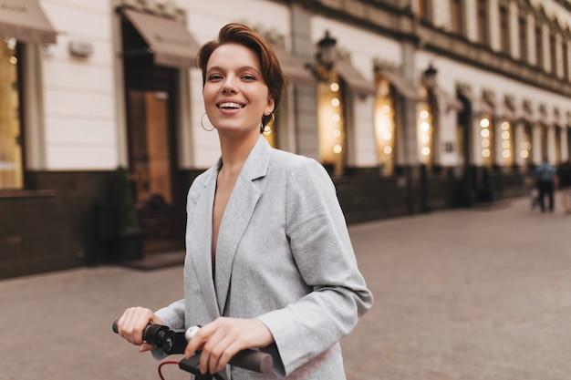 Dame souriante en tenue grise équitation scooter. enthousiaste jeune femme aux cheveux courts en veste surdimensionnée élégante sourit sincèrement et pose à l'extérieur