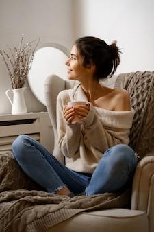 Dame souriante en vêtements à la mode intelligente est assise sur un fauteuil avec une tasse de thé.