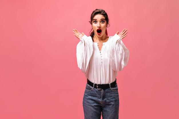Dame surprise en jeans et chemisier blanc se penche sur la caméra. fille aux lèvres rouges et dans des vêtements élégants posant sur fond isolé.
