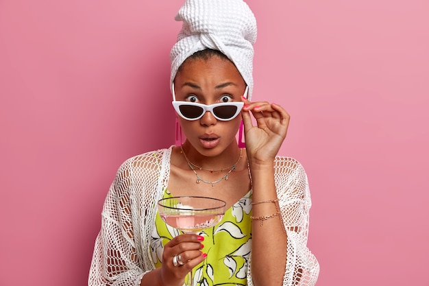 Dame surprise avec une peau et une manucure bien soignées, a l'air étonnée sous les lunettes de soleil, boit un cocktail, vêtue de vêtements domestiques, entend des nouvelles incroyables, isolées sur un mur rose.