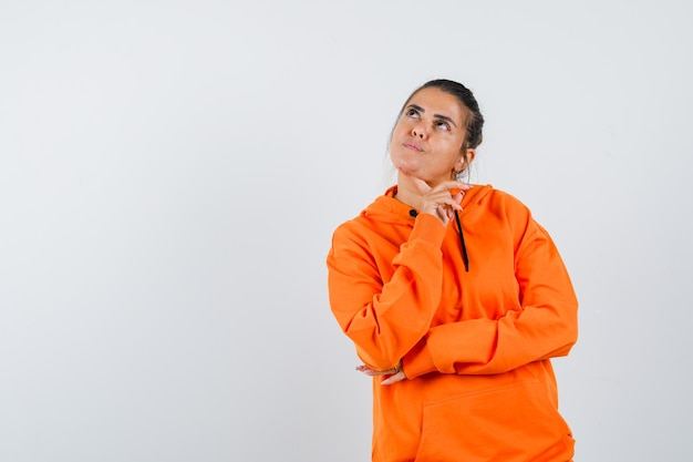 Dame en sweat à capuche orange soutenant le menton sur le doigt et l'air songeur