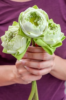 Dame tenant beau lotus en fleurs pour rendre hommage à bouddha