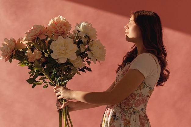 Dame tenant le bouquet de fleurs vue latérale