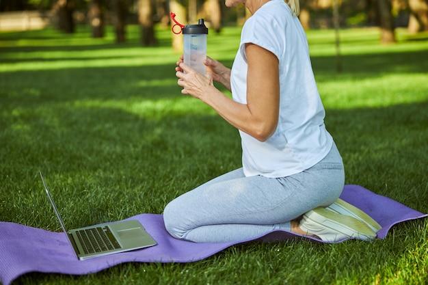 Dame en tenue de sport tenant une bouteille de boisson rafraîchissante assise sur un tapis de yoga avec un ordinateur portable moderne