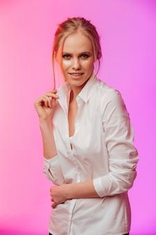 Dame vêtue d'une chemise blanche posant sur un mur rose.