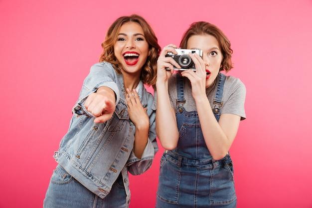 Des dames heureuses font des photos par caméra et pointent vers vous.