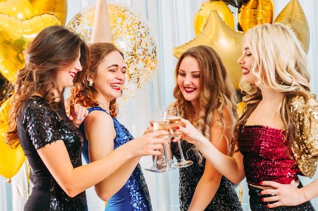Dames en robes à paillettes. filles heureuses tintant des verres de champagne, riant, s'amusant.