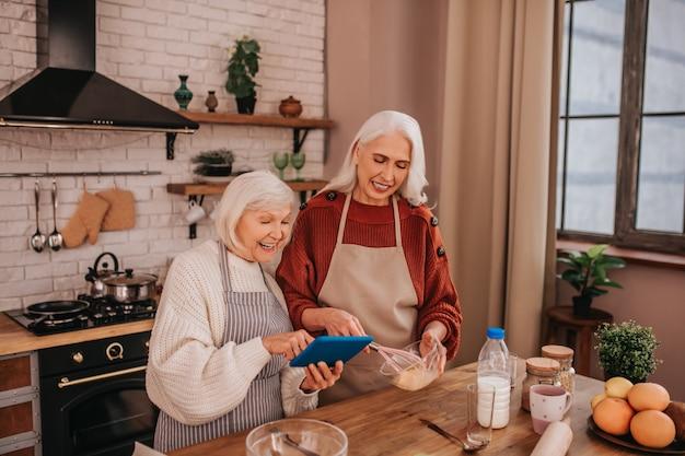 Dames souriantes aux cheveux gris en tabliers à la recherche d'une nouvelle recette en ligne