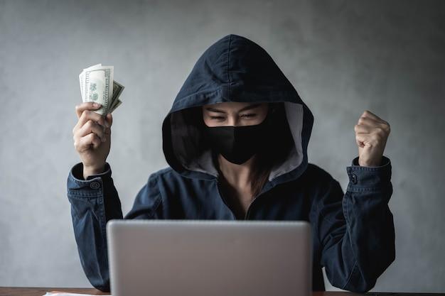 Dangerous hooded hacker détenait l'argent après un piratage réussi.