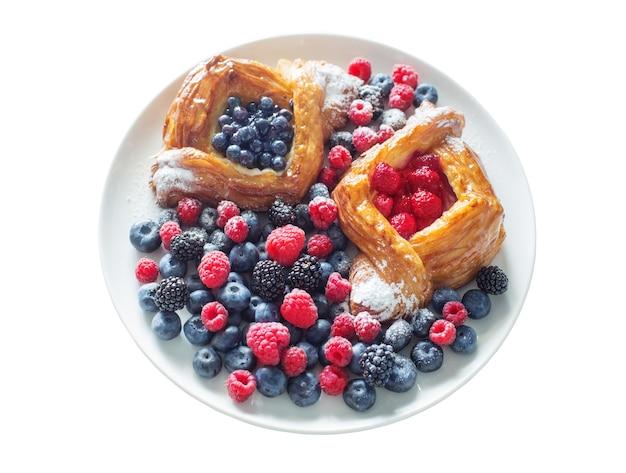 Danois aux framboises et aux bleuets sur une assiette ronde avec des baies isolées sur blanc