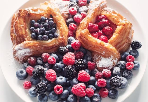 Danois aux framboises et aux bleuets sur une assiette ronde avec des baies sur un tableau blanc