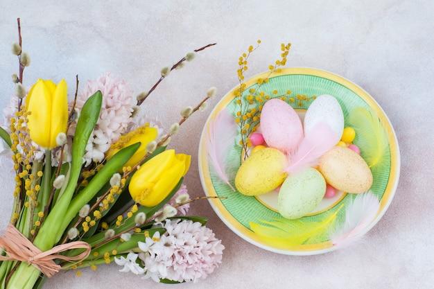 Dans une assiette d'oeufs de pâques et à côté d'un bouquet de jacinthes et de tulipes