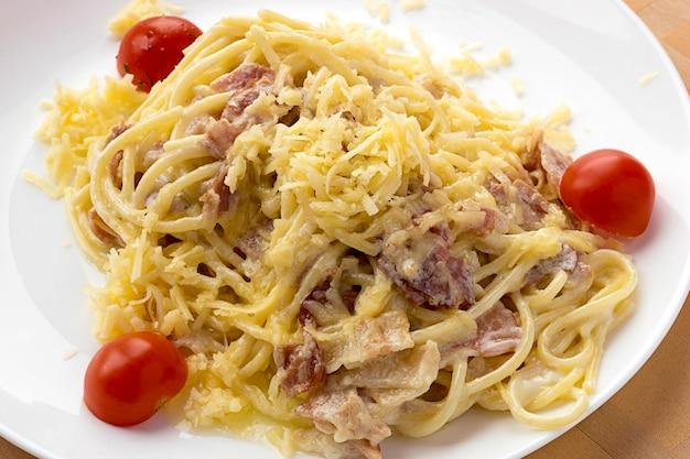 Dans l'assiette se trouvent des spaghettis carbonara aux tomates.