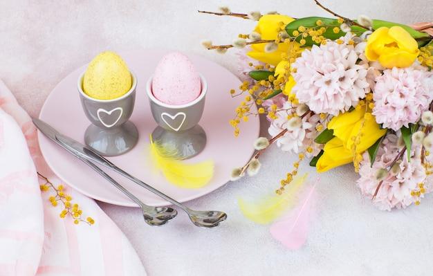 Dans une assiette sont deux œufs de pâques, deux cuillères et à côté d'un bouquet de jacinthes et de tulipes