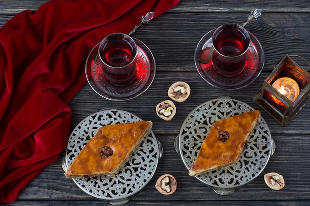 Dans des assiettes en argent baklava, noix, lanterne et thé. kareem ramadan.