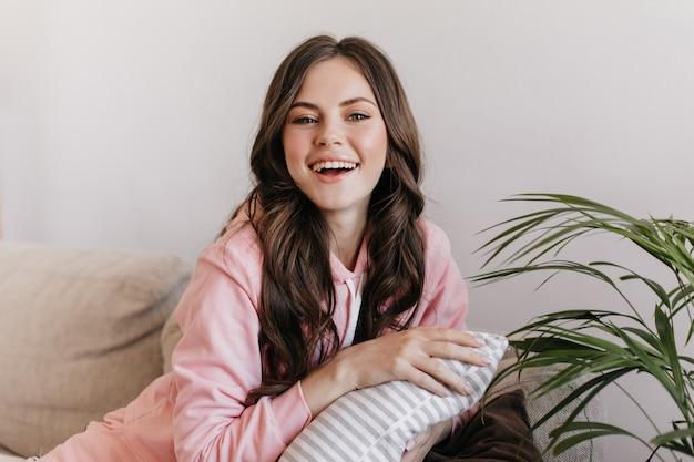 Dans une atmosphère chaleureuse et chaleureuse, sur un beau canapé près duquel il y a une grande fleur, posant joliment belle femme