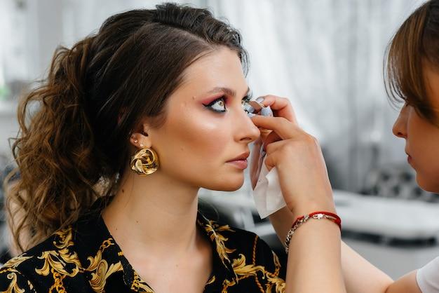 Dans Un Beau Salon De Beauté Moderne, Une Maquilleuse Professionnelle Maquille Une Jeune Fille. Beauté Et Mode. Photo Premium